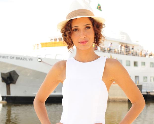 Carol com chapéu Fedora em cena de almoço de negócios no navio.